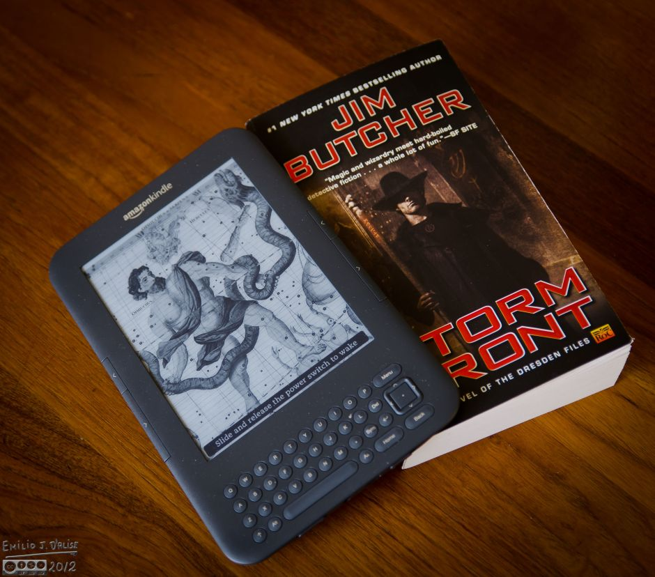 My Kindle Keyboard next to the first of 13 Harry Dresden books