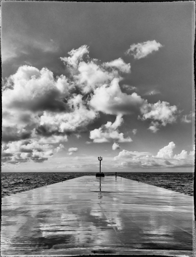 Monochrome version of red signal at the end of a breakwater.