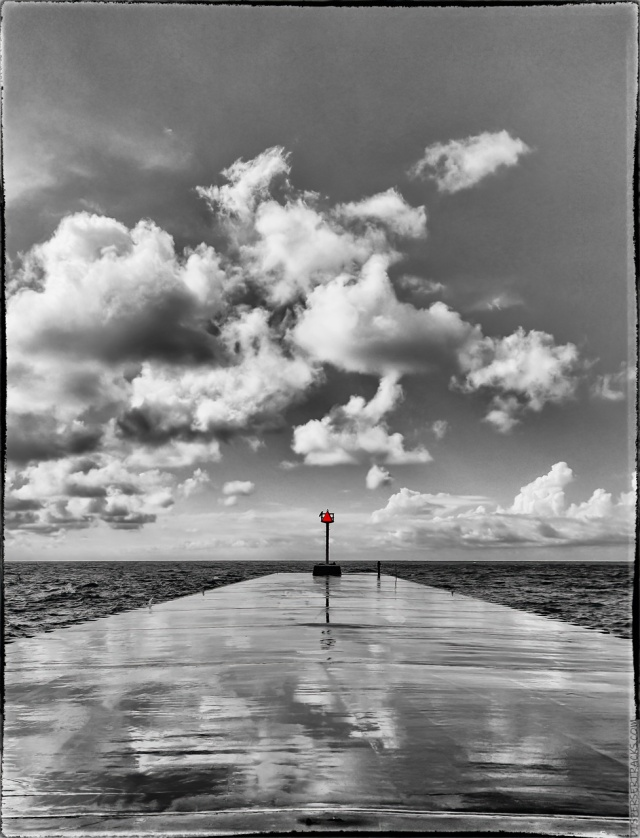 Monochrome versions of red signal at the end of a breakwater.