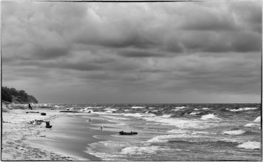 Lakeshore in monochrome with distant seated figure looking out at the waves