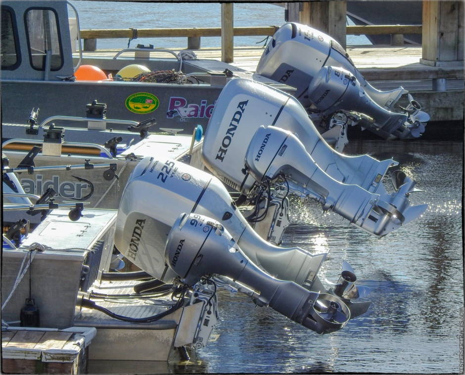 three boats with their outboard motors lifted out of the water
