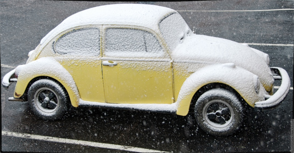 Yellow VW Beetle covered in snow