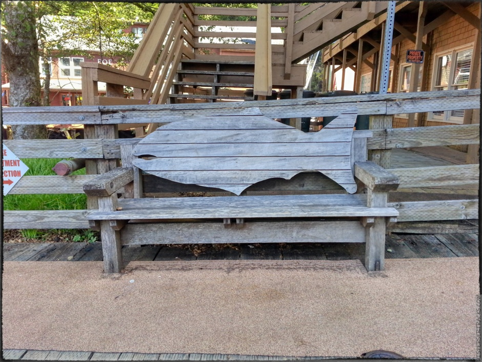 A woodden bench with the shape of a salmon for the back support